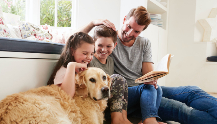Father Reading To Daughters With Dog